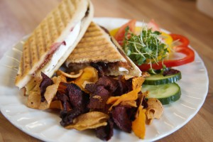 Hot panini served with vegetable chips and a small salad